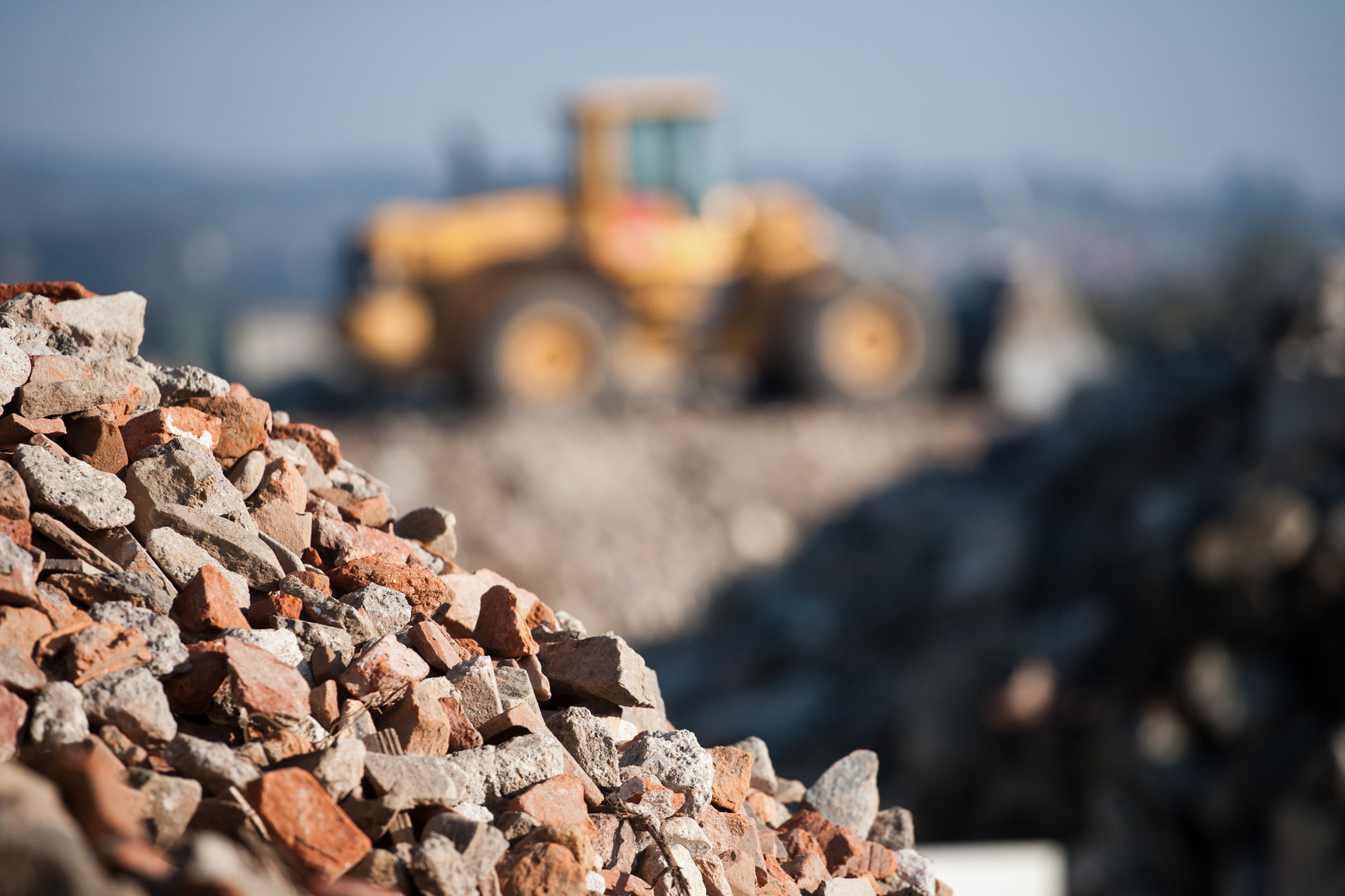 Pile of rocks with excavator in background